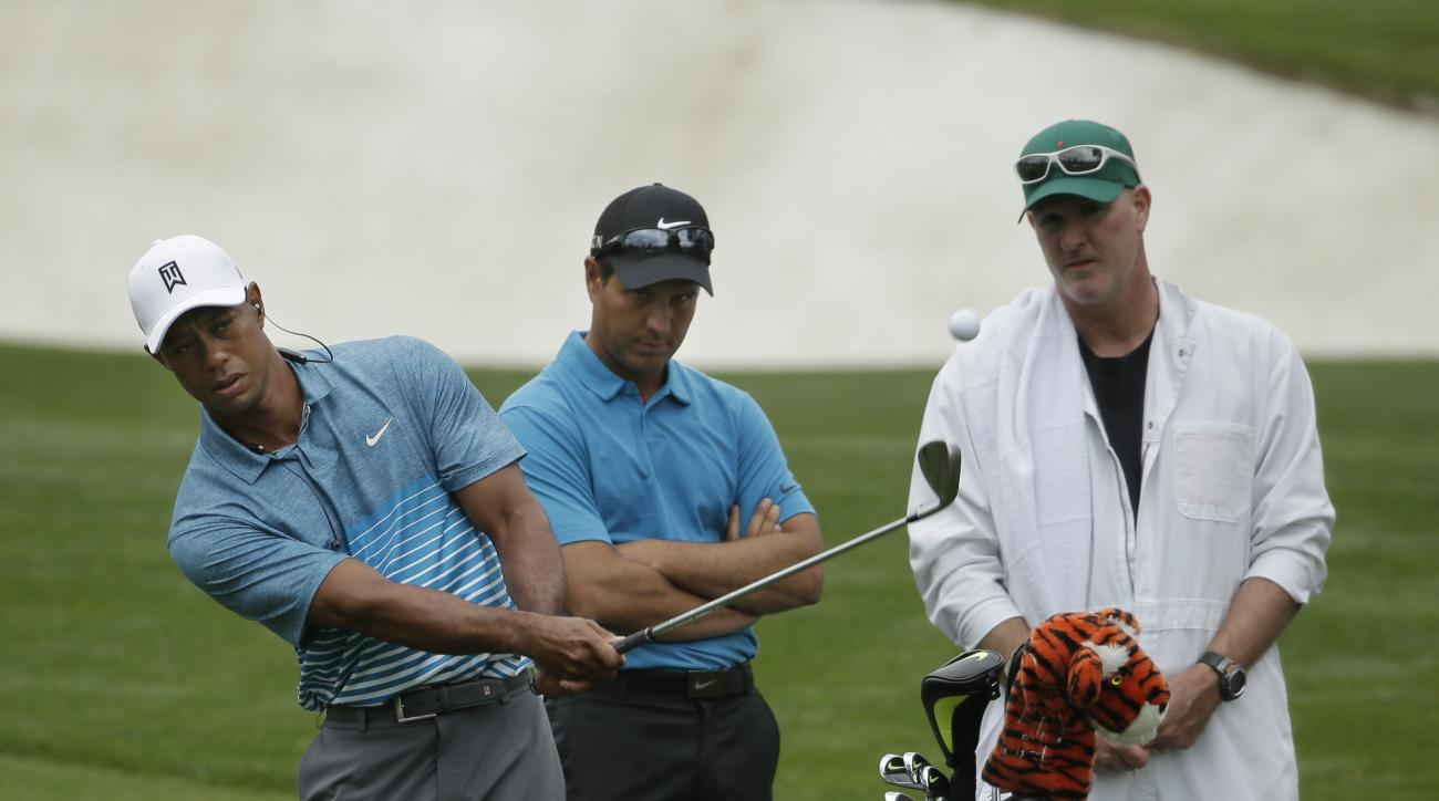Tiger Woods is watched on the driving range by coach Chris Como during the 2015 Masters.