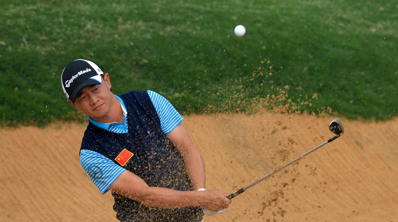 Huang Wenyi plays a shot from a bunker during the 2013 BMW Masters in Shanghai, China.
