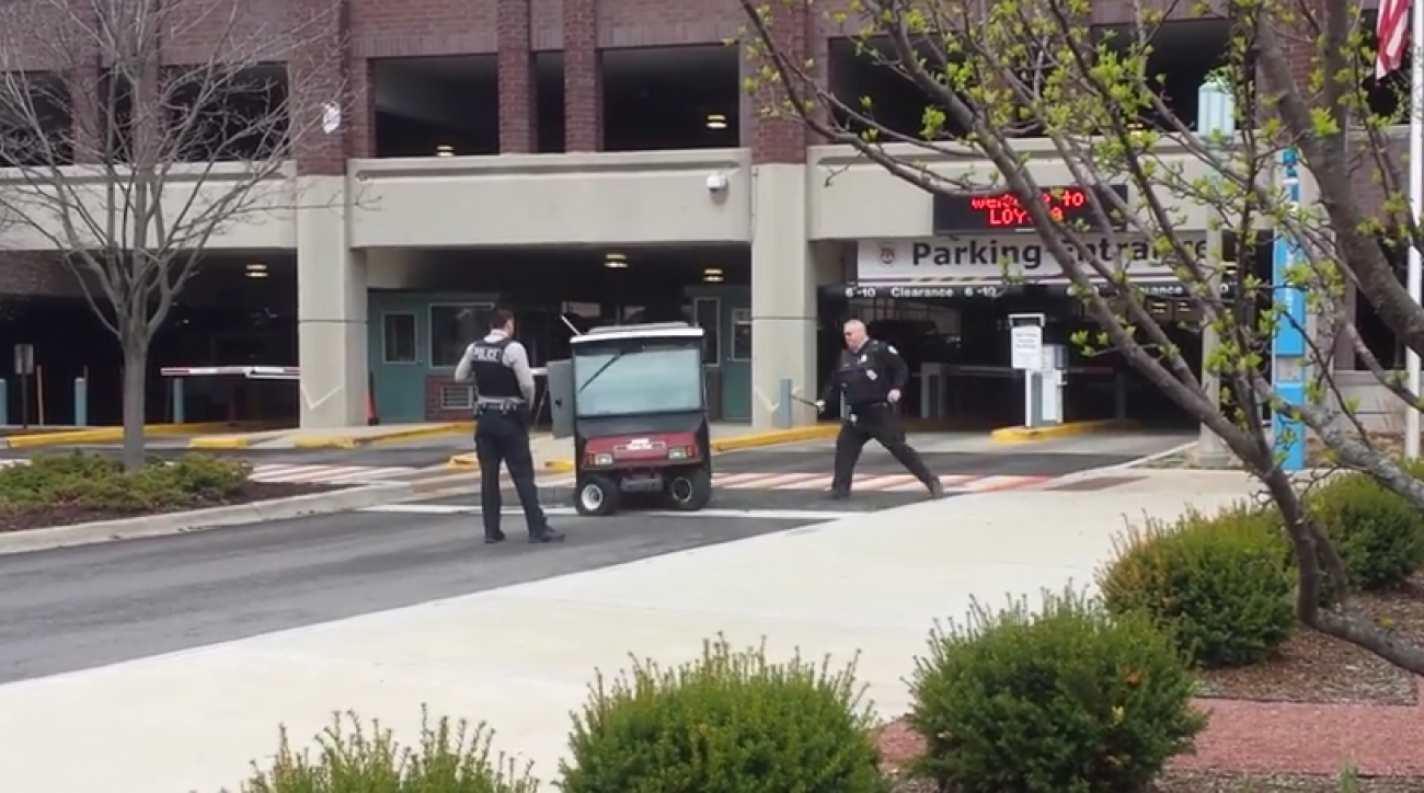 Two campus police offers try to wrangle the errant golf cart.