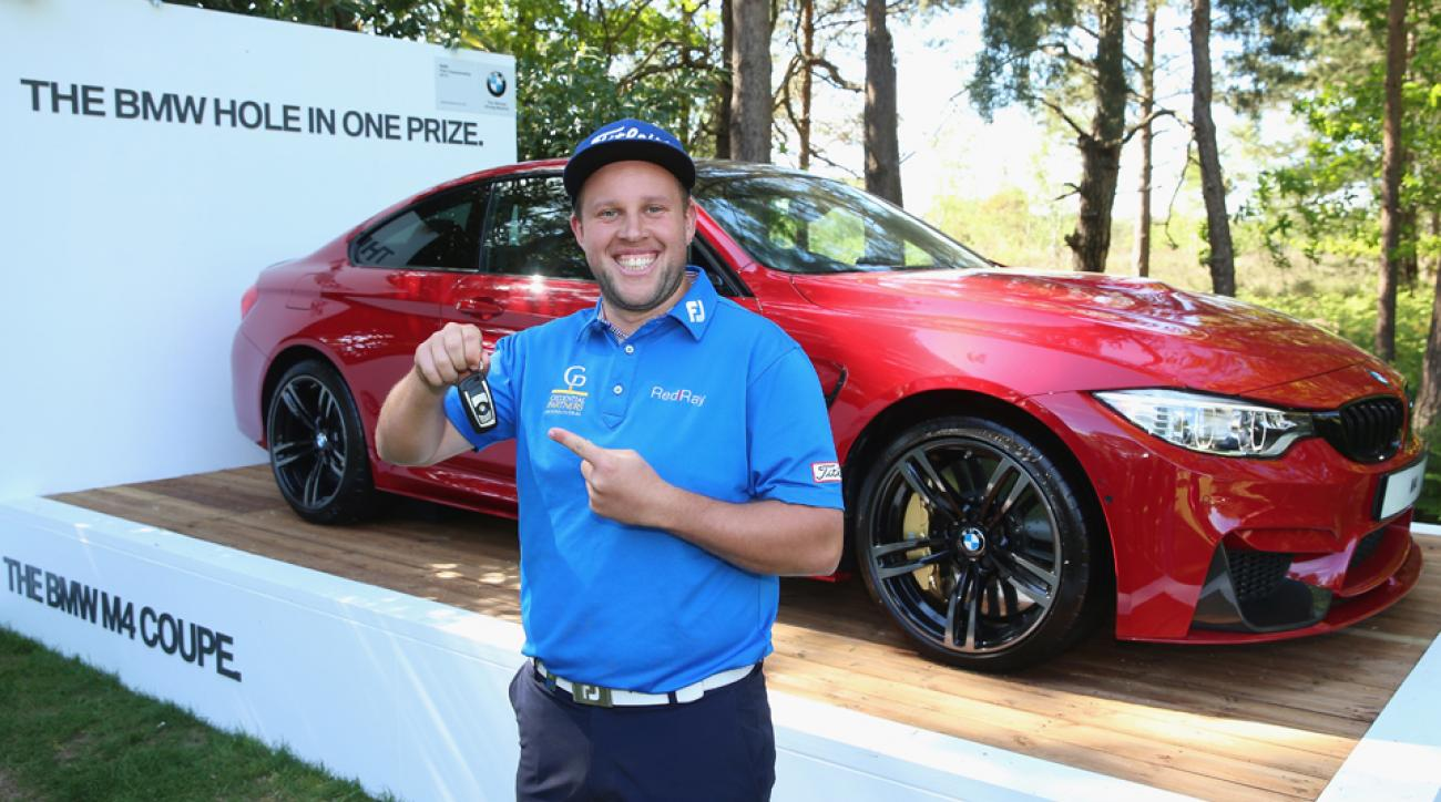 Andrew Johnston of England poses with the keys to his new BMW M4 Coupe after his hole-in-one on the 10th hole during the BMW PGA Championship at Wentworth on May 21, 2015, in Virginia Water, England.