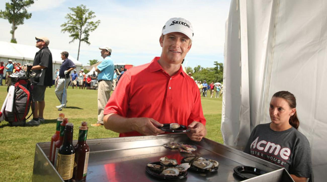David Toms samples Acme Oyster House's speciality near the first tee at the 2015 Zurich Classic of New Orleans.