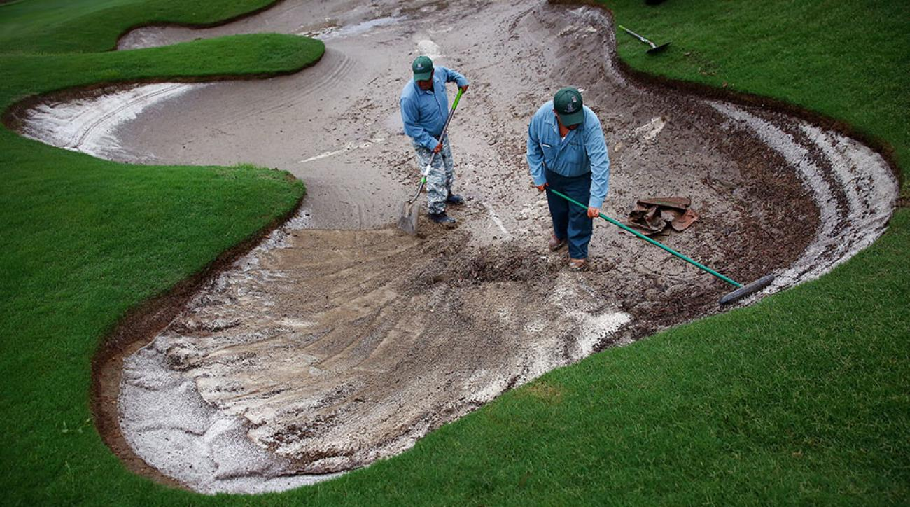Grounds crew staff work to repair a flooded bunker on the 17th hole after heavy rains delayed Round Two of the AT&T Byron Nelson at the TPC Four Seasons Resort Las Colinas on May 29, 2015 in Irving, Texas.
