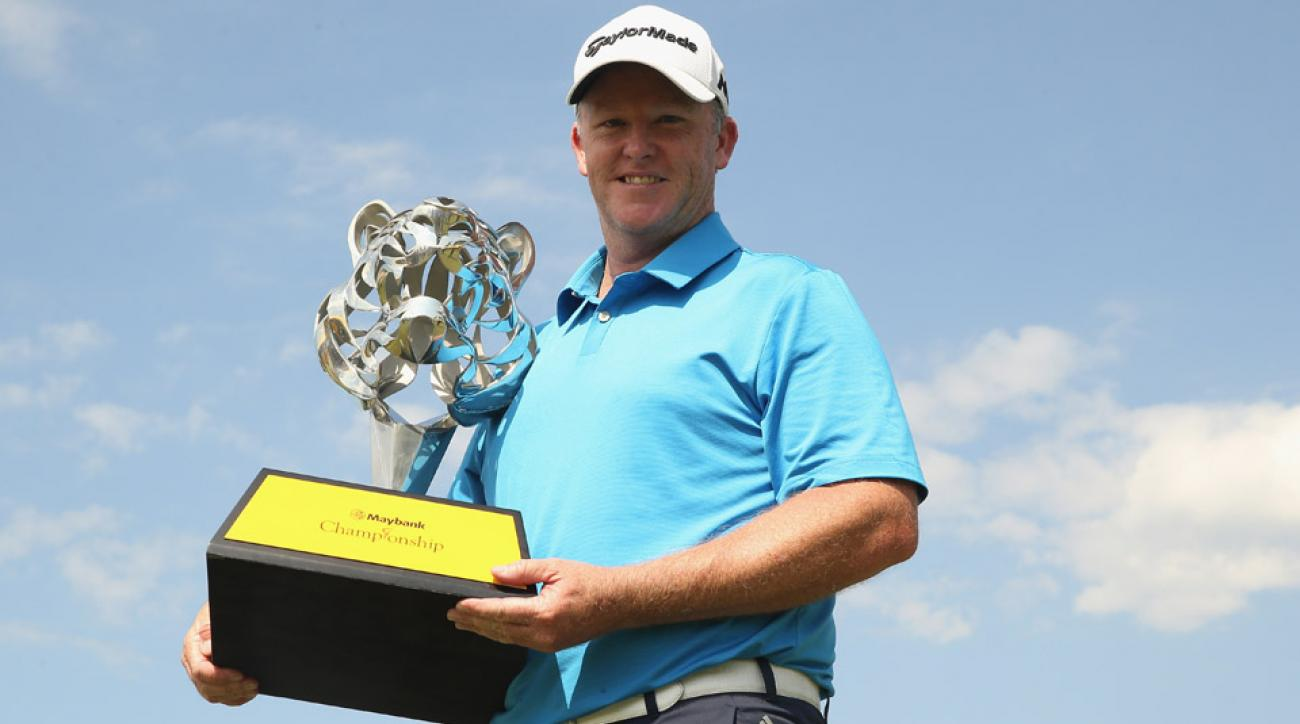 Marcus Fraser celebrates with the trophy after winning the Maybank Championship Malaysia at Royal Selangor Golf Club on Feb. 21, 2016, in Kuala Lumpur, Malaysia.