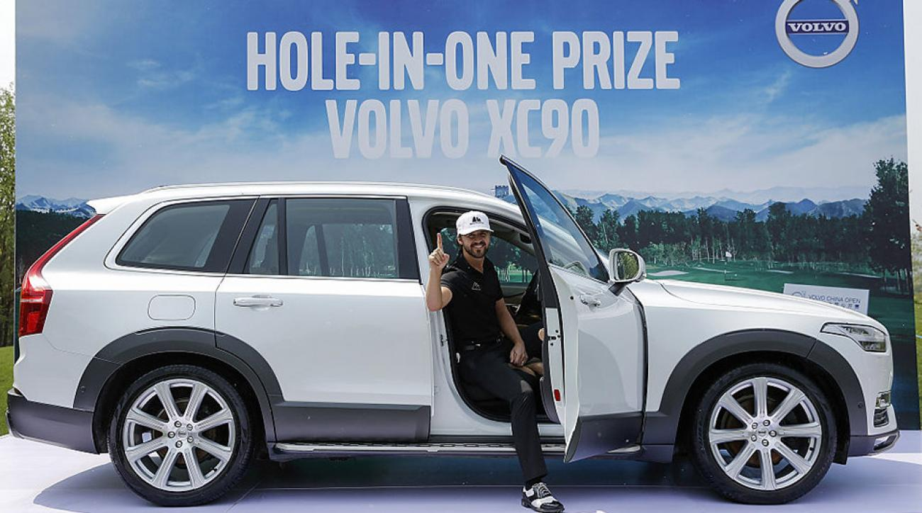 Rikard Karlberg of Sweden celebrates the car he won for a hole in one during the Volvo China Open.