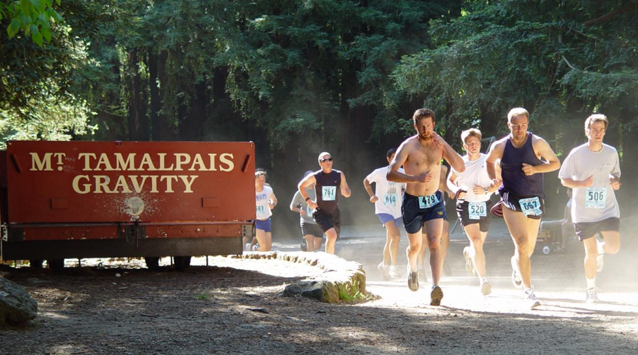 Runners in the Dipsea Race pass a Gravity Car in Mill Valley's Old Mill Park on Mount Tamalpais in Northern California.