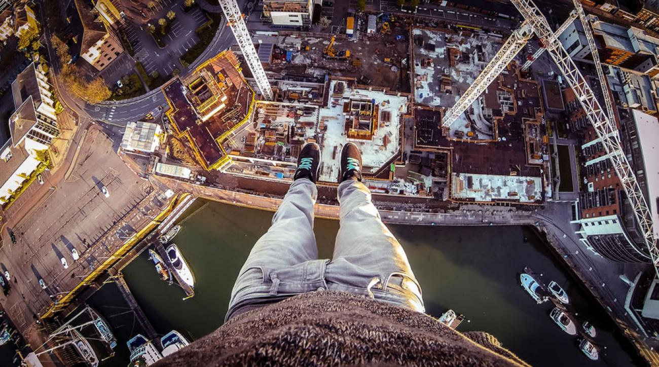 Professional Adventurer James Kingston hangs above the world in one of his many stunts. Below, he's featured doing a back flip on the top of a 390-foot bridge.