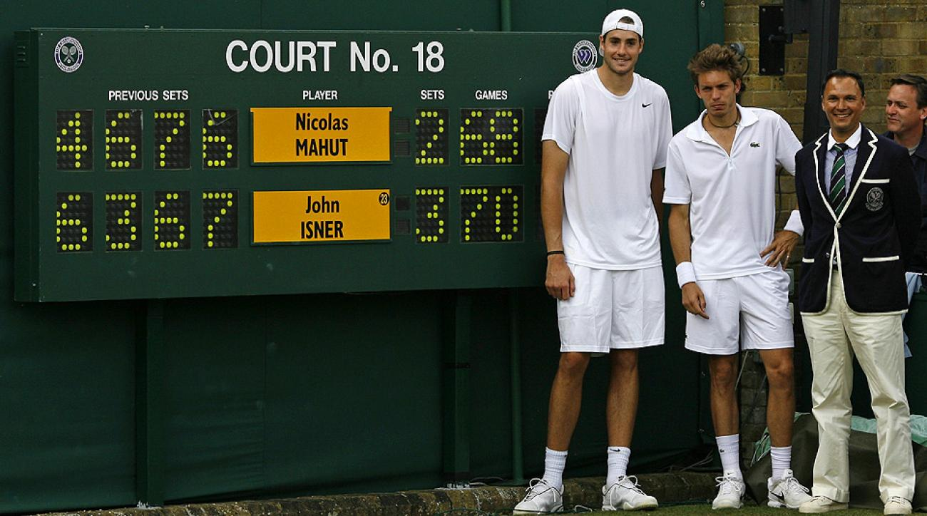 John Isner and Nicolas Mahut pose next to the scoreboard after finishing the longest tennis match ever at Wimbledon in 2010.