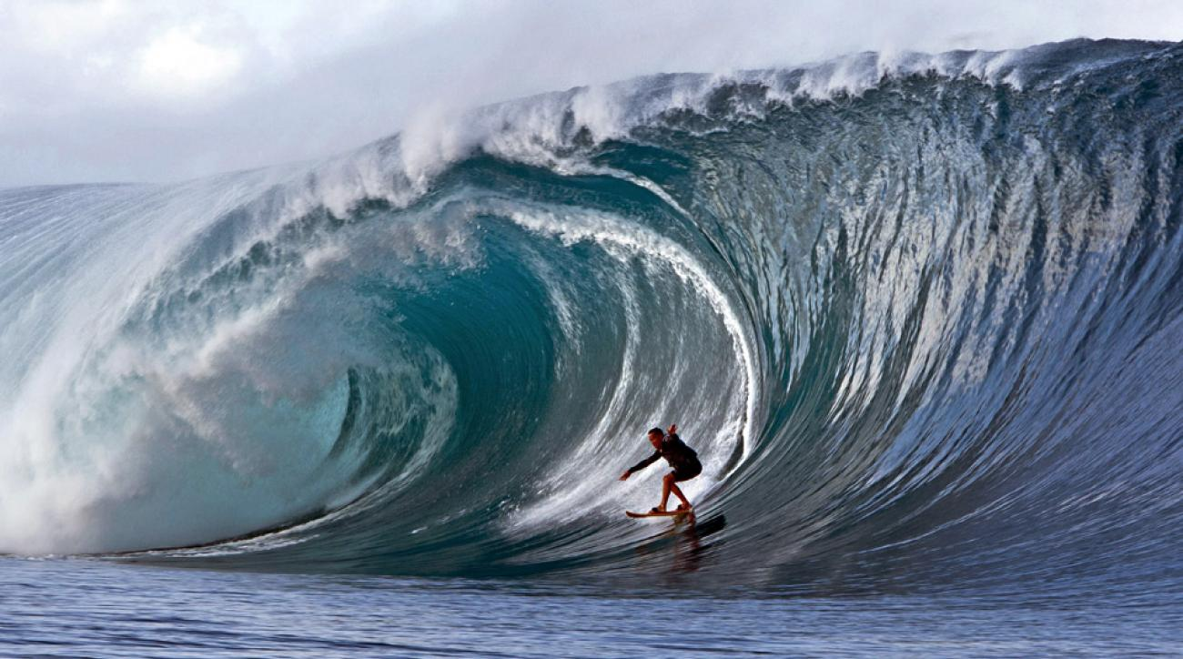 A surfer rides a wave at Teahupo'o, a village on the southwest coast of Tahiti. Professional surfers from all over the world regularly descend upon Teahupo'o to ride the local waves that can easily rise above 25 feet tall.