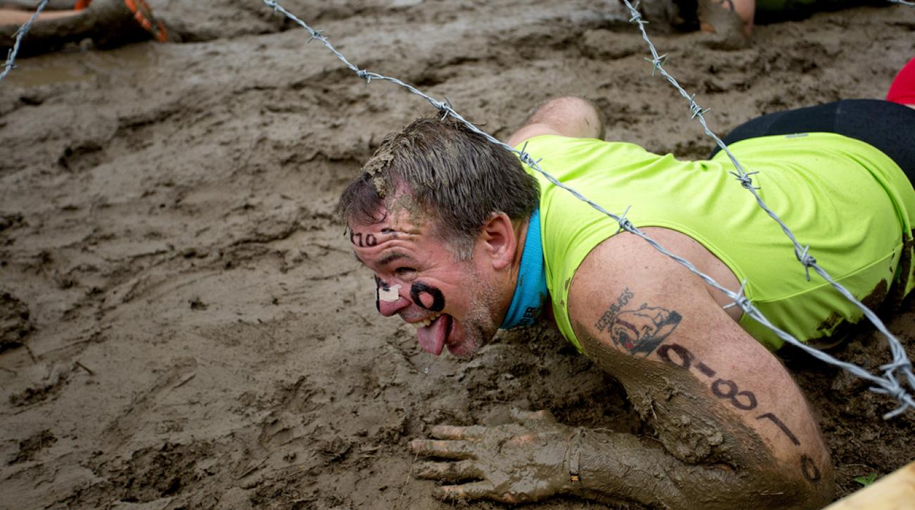 """A competitor in the Tough Mudder crawls through the """"Kiss the Mud"""" hazard."""