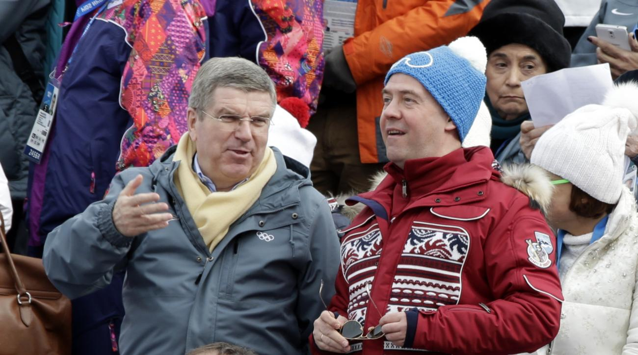 International Olympic Committee Thomas Bach, left, speaks to Russian Prime Minister Dmitry Medvedev, right, at the Alpine ski venue during the men's downhill at the Sochi 2014 Winter Olympics, Sunday, Feb. 9, 2014, in Krasnaya Polyana, Russia. (AP Photo/Gero Breloer)
