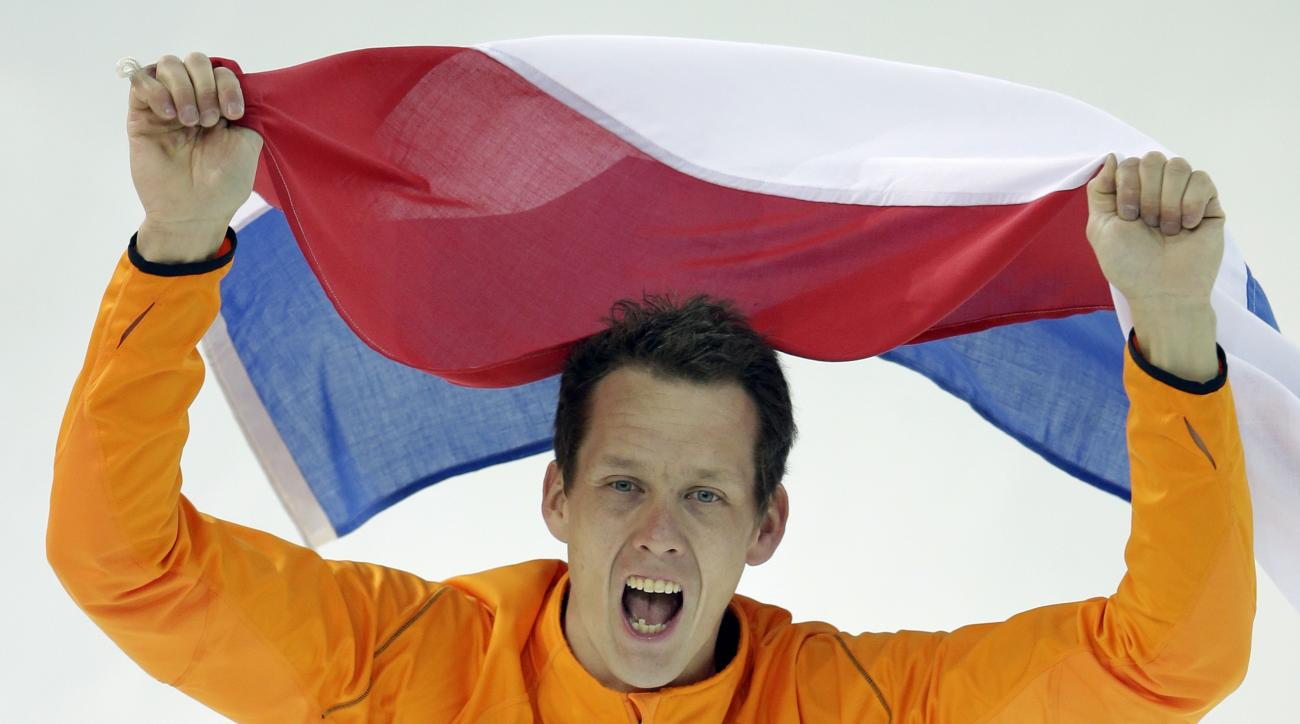 Stefan Groothuis of the Netherlands holds his national flag and celebrates after winning the gold in the men's 1,000-meter speedskating race at the Adler Arena Skating Center at the 2014 Winter Olympics in Sochi, Russia, Wednesday, Feb. 12, 2014. (AP Photo/Patrick Semansky)