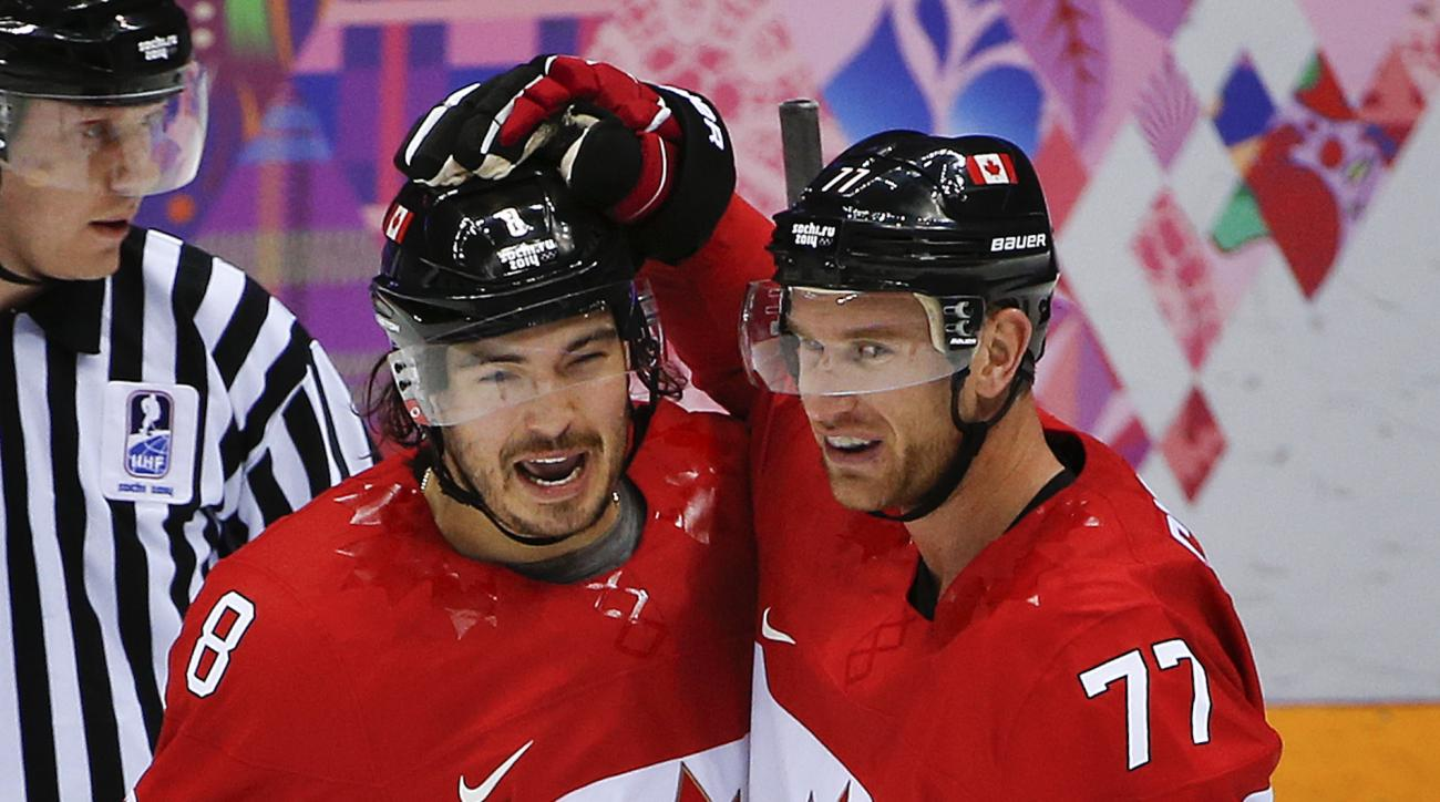 Canada defenseman Drew Doughty, left, celebrates with forward Jeff Carter after scoring a goal against Finland in the first period of a men's ice hockey game at the 2014 Winter Olympics, Sunday, Feb. 16, 2014, in Sochi, Russia. (AP Photo/Julio Cortez)