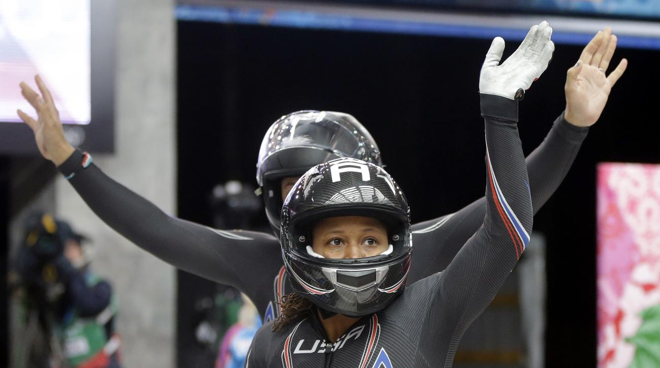The team from the United States USA-1, piloted by Elana Meyers with brakeman Lauryn Williams, front, wave to fans after their first run during the women's two-man bobsled competition at the 2014 Winter Olympics, Tuesday, Feb. 18, 2014, in Krasnaya Polyana, Russia. (AP Photo/Dita Alangkara)