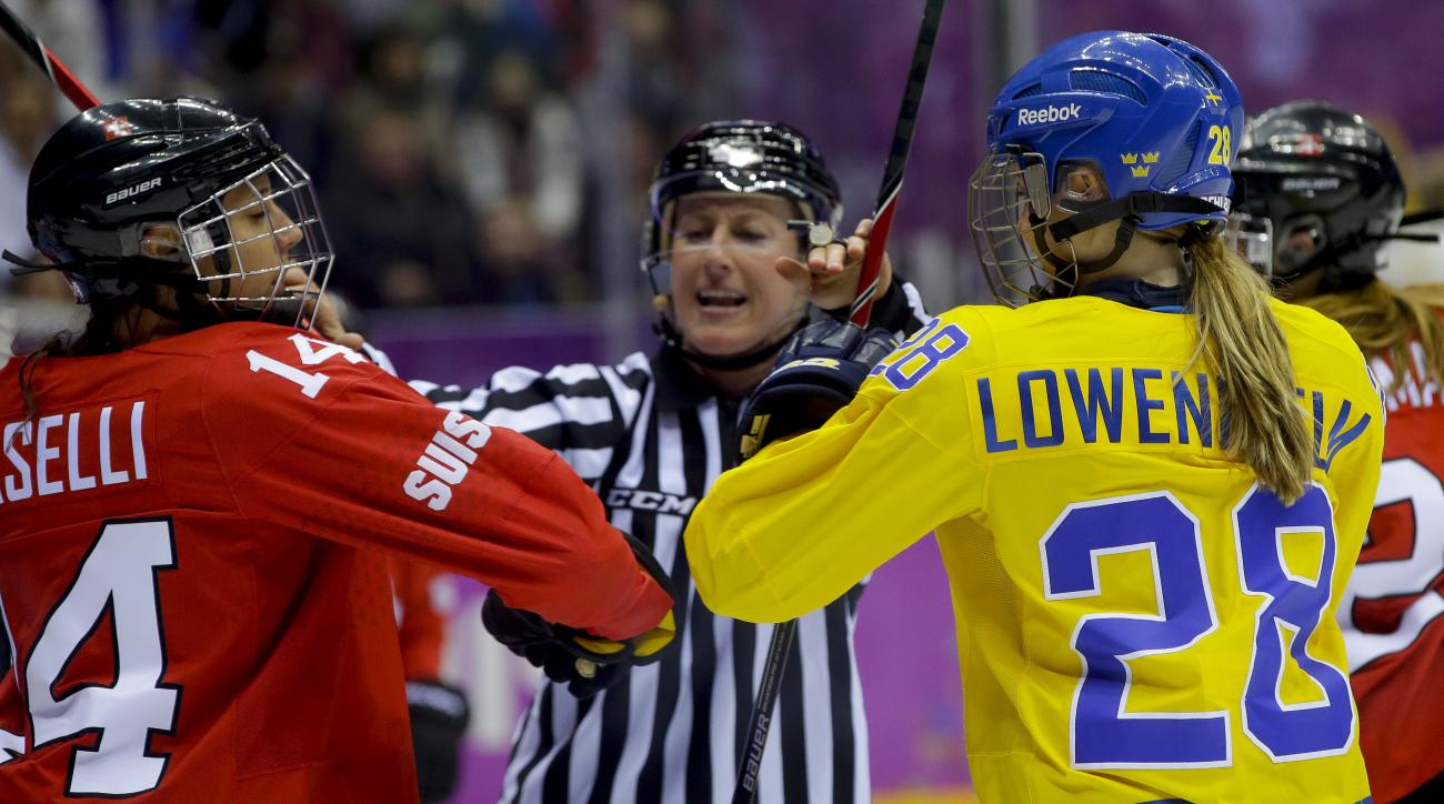 An official breaks up a scuffle between Evelina Raselli of Switzerland (14) and Michelle Lowenhielm of Sweden (28) during the second period of the women's bronze medal ice hockey game at the 2014 Winter Olympics, Thursday, Feb. 20, 2014, in Sochi, Russia. (AP Photo/Matt Slocum)