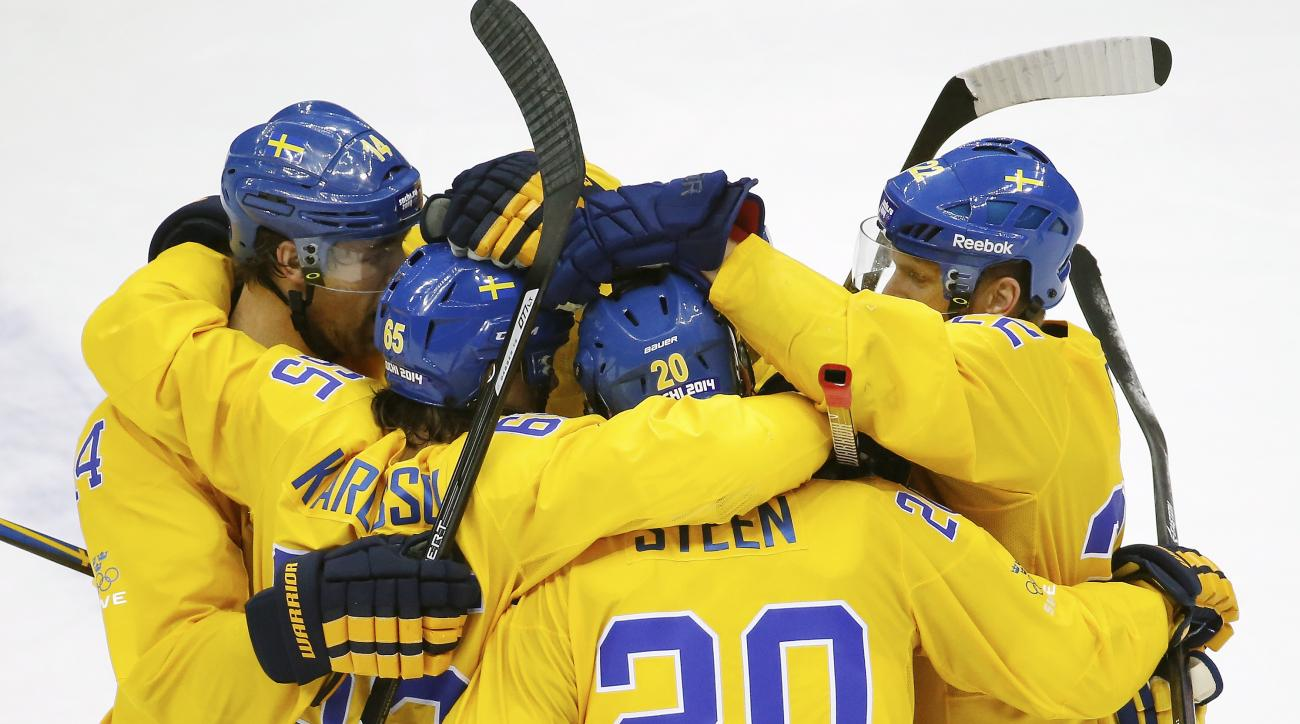 Members of Team Sweden celebrate Erik Karlsson's (65) goal against Finland in the second period of the men's semifinal ice hockey game at the 2014 Winter Olympics, Friday, Feb. 21, 2014, in Sochi, Russia. (AP Photo/Mark Humphrey)