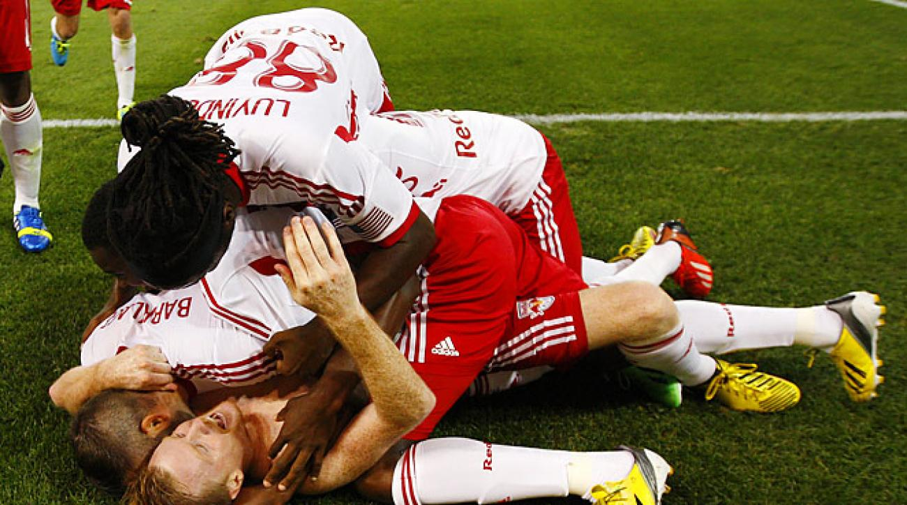 Dax McCarty is mobbed by Red Bulls teammates after scoring a stoppage-time winner against RSL.