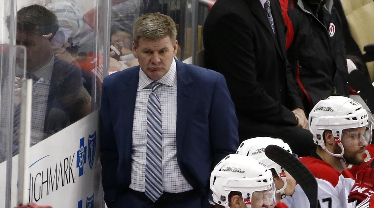 Carolina Hurricanes head coach Bill Peters stands behind his bench during an NHL hockey game against the Pittsburgh Penguins in Pittsburgh, Thursday, March 17, 2016. (AP Photo/Gene J. Puskar)