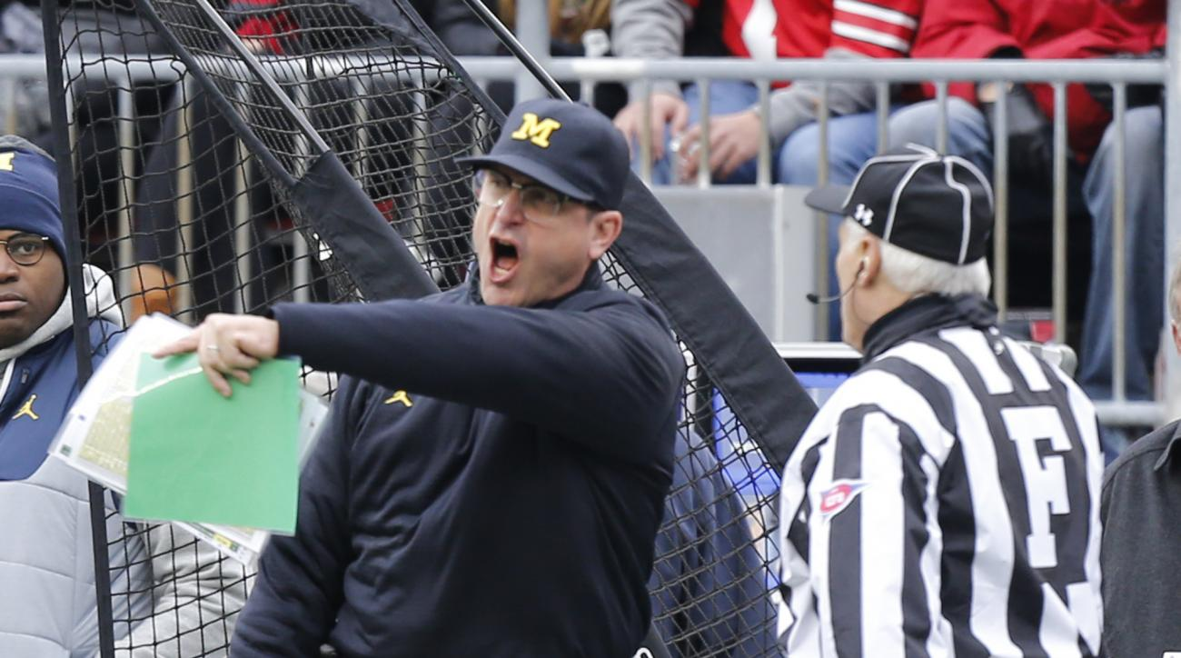 Michigan head coach Jim Harbaugh, left, yells at the field judge during the first half of an NCAA college football game  against Ohio State, Saturday, Nov. 26, 2016, in Columbus, Ohio. Ohio State beat Michigan 30-27 in double overtime. (AP Photo/Jay LaPre