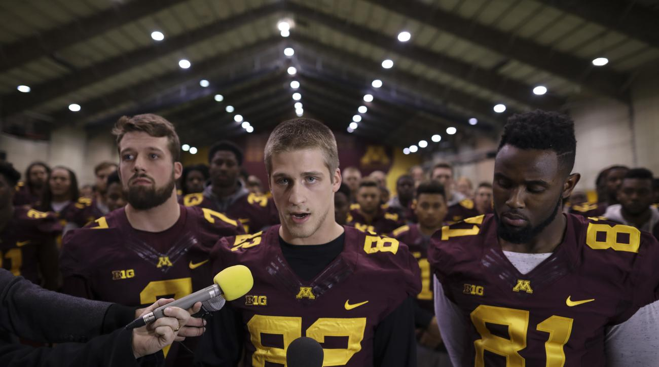 FILE - In this Dec. 15, 2016, file photo, University of Minnesota wide receiver Drew Wolitarsky, flanked by quarterback Mitch Leidner, left, and tight end Duke Anyanwu stands in front of other team members as he reads a statement on behalf of the players