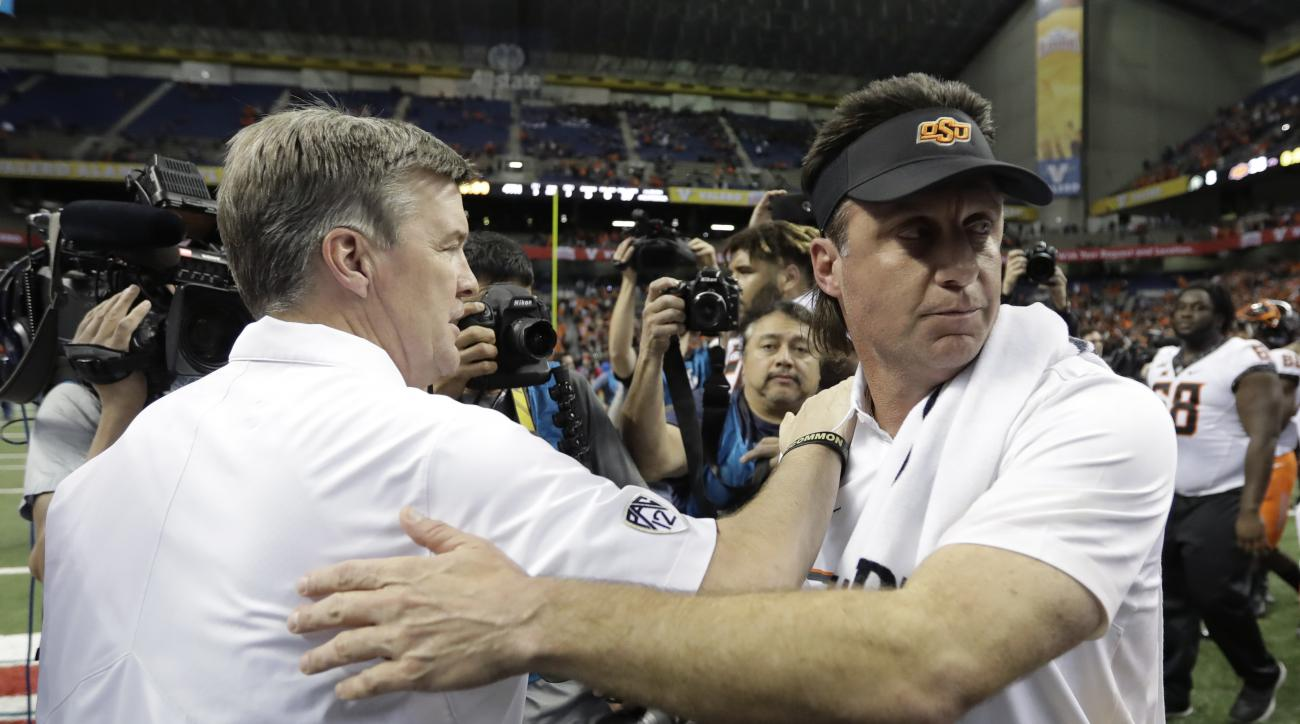 Colorado coach Mike MacIntyre, left, and Oklahoma State coach Mike Gundy, right, meet at midfield following the Alamo Bowl NCAA college football game, Thursday, Dec. 29, 2016, in San Antonio. Oklahoma State won 38-8. (AP Photo/Eric Gay)