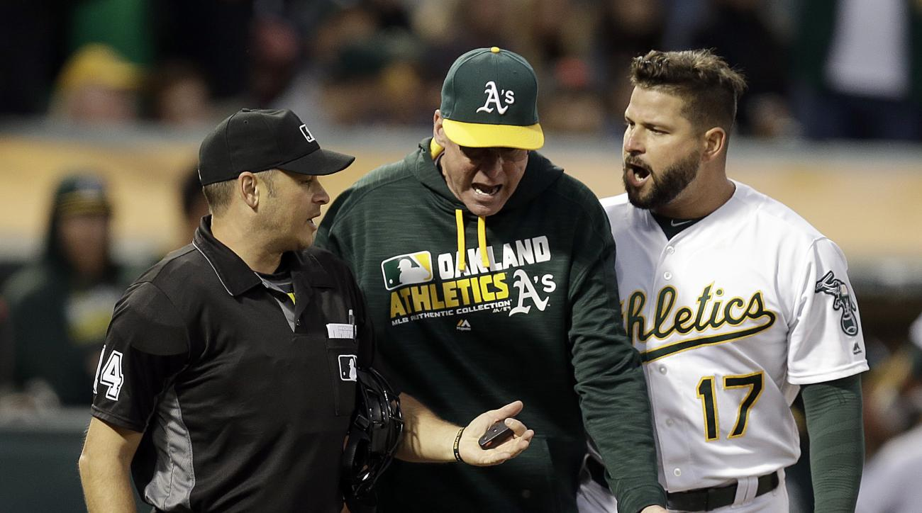 Oakland Athletics manager Bob Melvin, center, and Athletics' Yonder Alonso (17) argue with home plate umpire Mark Wegner after being ejected during the fourth inning of a baseball game Friday, July 15, 2016, in Oakland, Calif. (AP Photo/Ben Margot)