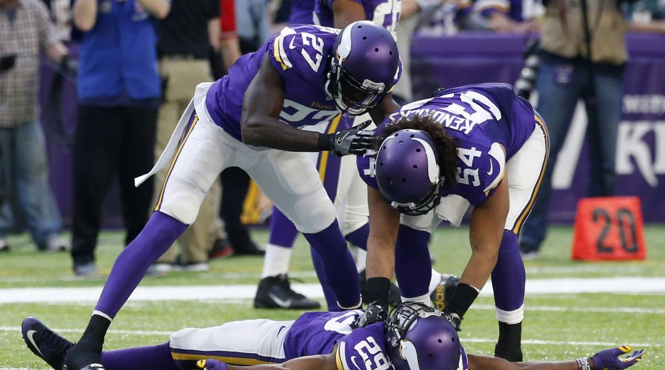 Minnesota Vikings cornerback Xavier Rhodes (29) celebrates with teammate Jayron Kearse (27) and Eric Kendricks (54) after intercepting a pass during the second half of an NFL football game against the Arizona Cardinals Sunday, Nov. 20, 2016, in Minneapoli