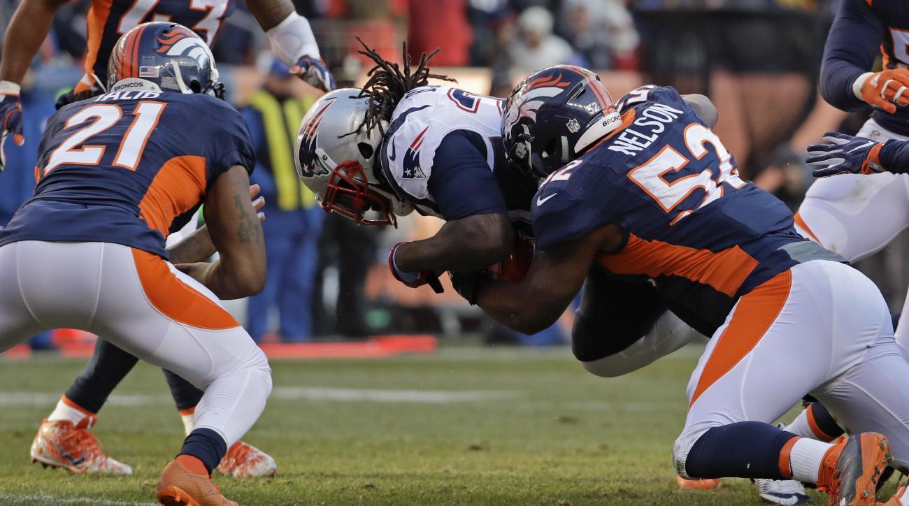 New England Patriots running back LeGarrette Blount scores between Denver Broncos cornerback Aqib Talib, left, and inside linebacker Corey Nelson during the first half of an NFL football game Sunday, Dec. 18, 2016, in Denver. (AP Photo/Jack Dempsey)