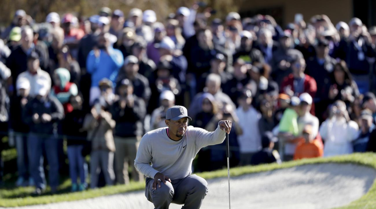 FILE - In this Friday, Jan. 27, 2017, file photo, Tiger Woods looks over his ball on the 18th hole of the North Course during the second round of the Farmers Insurance Open golf tournament at Torrey Pines Golf Course in San Diego. Woods has taken his tale