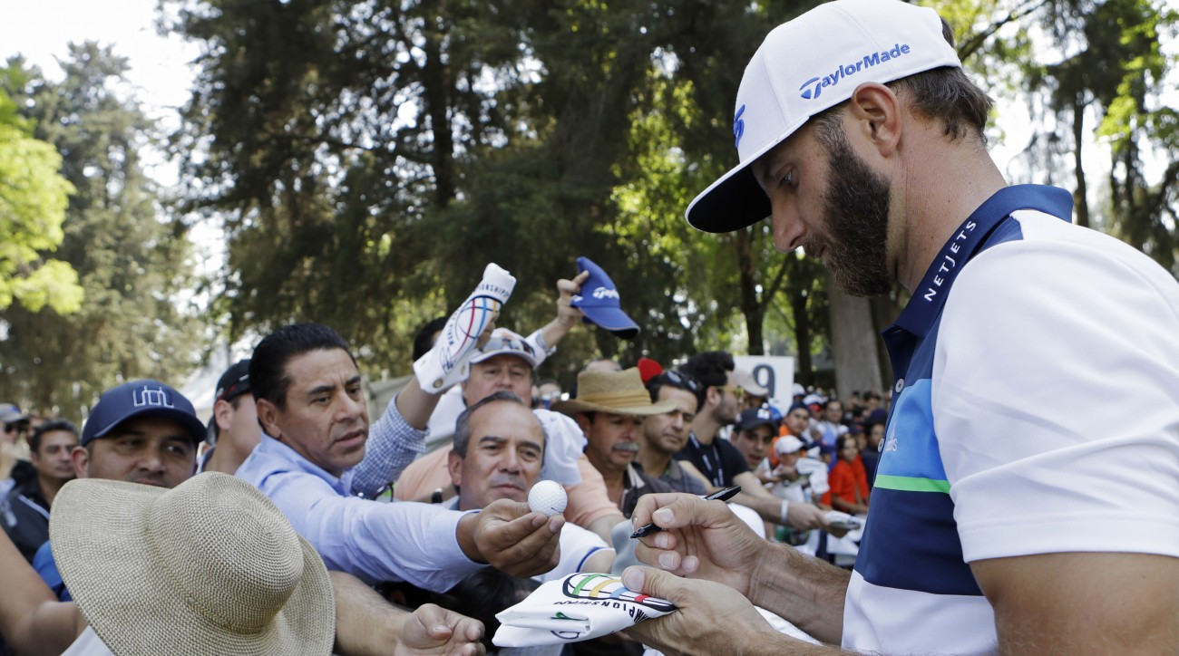 Dustin Johnson signs autographs for fans as he leaves the 9th hole after practicing on the high-altitude course at Chapultepec Golf Club a day before the start of the WGC-Mexico.