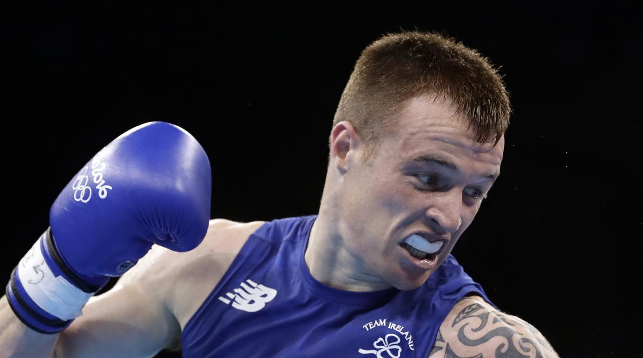 FILE - In this file photo dated Sunday, Aug. 7, 2016, Ireland's Steven Donnelly, fights Algeria's Zohir Kedache during a men's welterweight 69-kg boxing match at the 2016 Summer Olympics in Rio de Janeiro, Brazil. The International Olympic Committee (IOC)