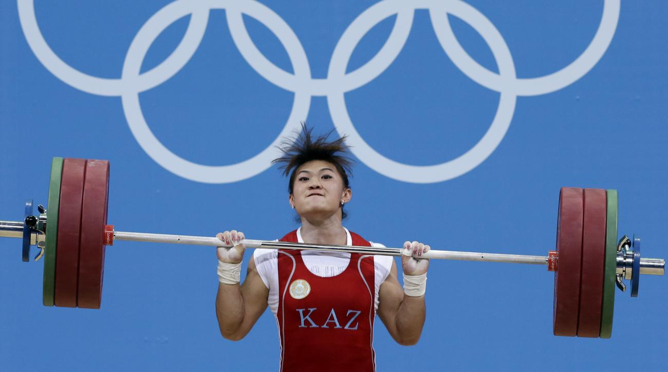 FILE - A Tuesday, July 31, 2012, photo from files of Maiya Maneza of Kazakhstan competing during the women's 63-kg, group A, weightlifting competition at the 2012 Summer Olympics, in London. Three female weightlifters from Kazakhstan, Maiya Maneza, Zulfiy
