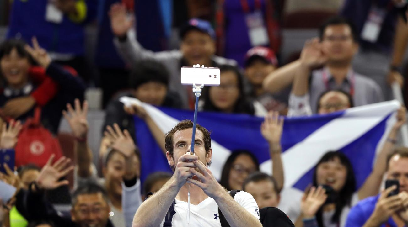 Andy Murray of Britain takes a selfie with spectators after winning his men's singles against Andreas Seppi of Italy at the China Open tennis tournament at the Diamond Court in Beijing, Tuesday, Oct. 4, 2016. (AP Photo/Andy Wong)