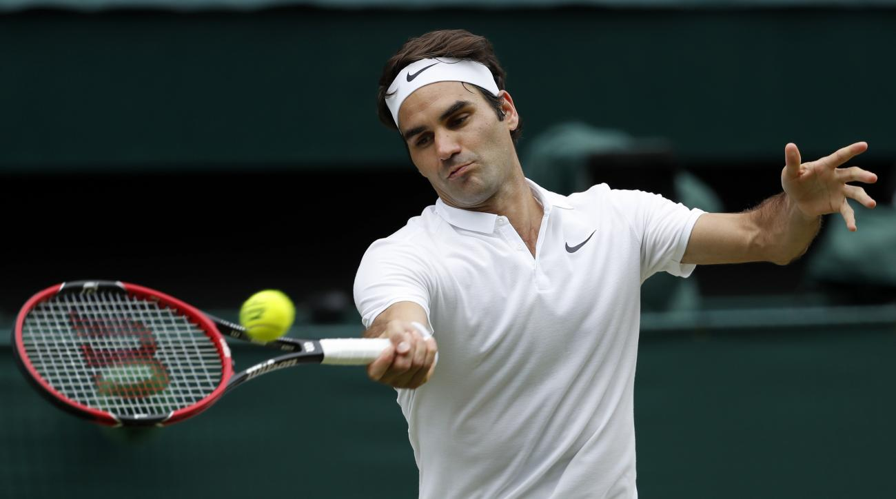 FILE - In this July 8, 2016, file photo, Roger Federer of Switzerland returns to Milos Raonic of Canada during their men's semifinal singles match at the Wimbledon Tennis Championships in London. Federer will return to competitive tennis at the Hopman Cup