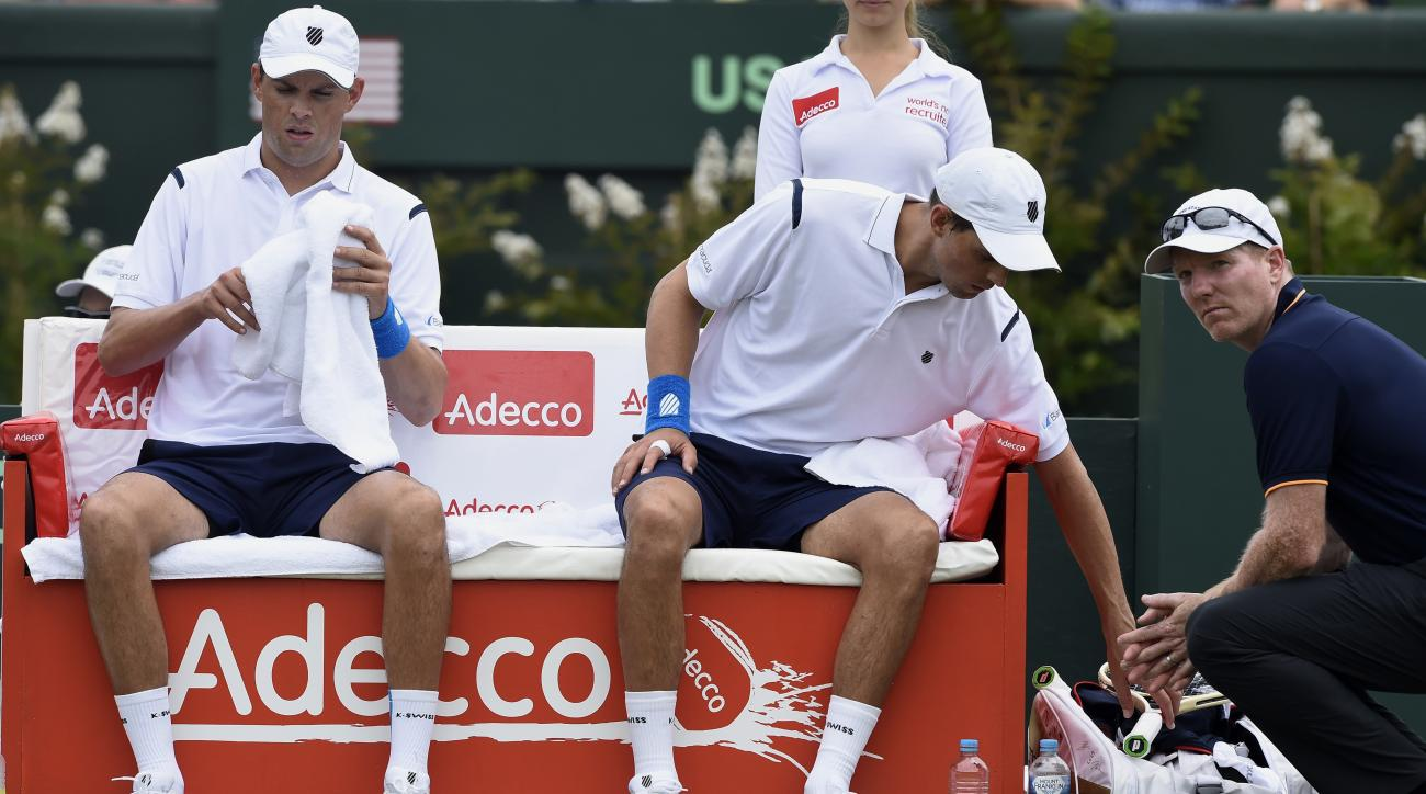 FILE - In this March 5, 2016 file photo, Jim Courier, right, captain of the United States Davis Cup team, talks to doubles players Bob, left, and Mike Bryan while playing against Australia's Lleyton Hewitt and John Peers during their Davis Cup doubles mat