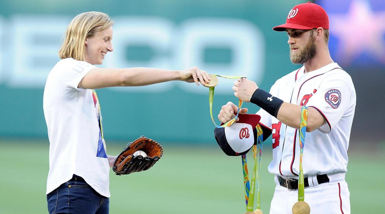 Katie Ledecky throws out first pitch at Nationals game, Bryce Harper holds her medals