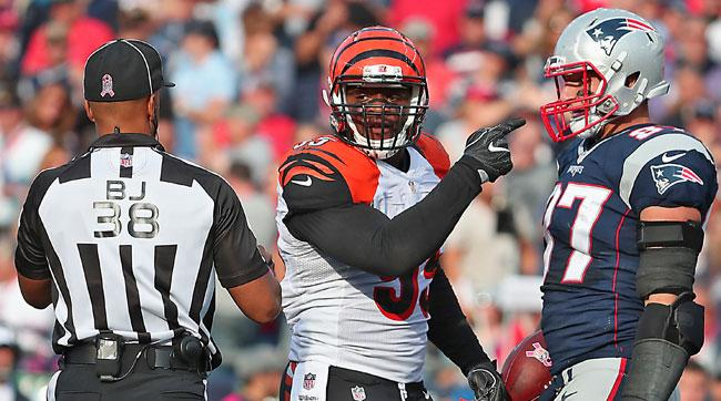 An official separates Bengals linebacker Vontaze Burfict and Patriots tight end Rob Gronkowski in the fourth quarter of Sunday's game.