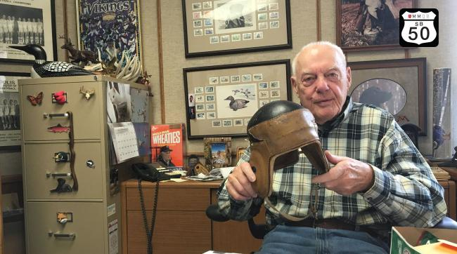 In his office at Vikings headquarters, Bud Grant shows off his father's 1920s-era NFL leather helmet.