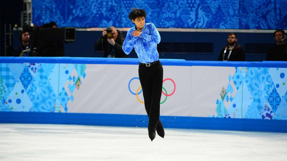 Japan's Yuzuru Hanyu completes a jump en route to the first 100-point score in the men's figure skating short program.