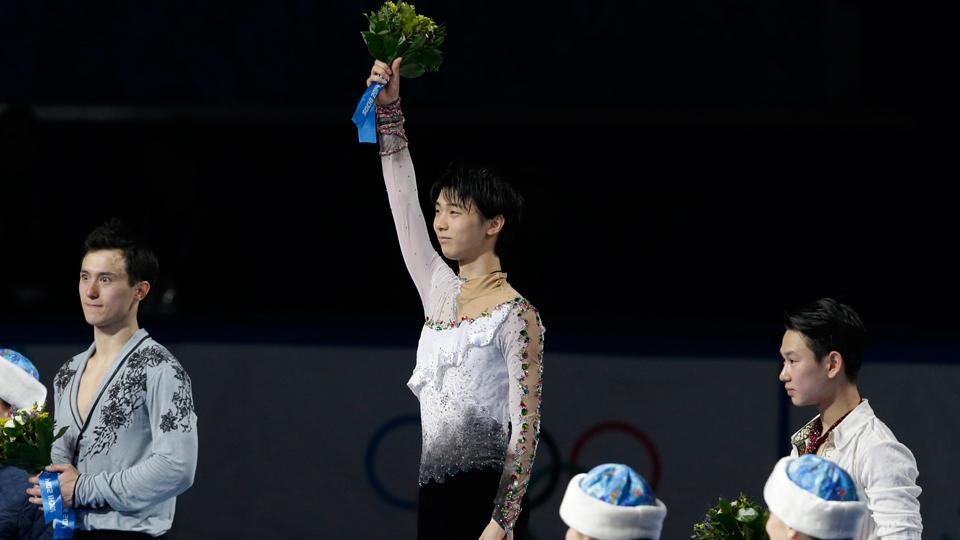Yuzuru Hanyu of Japan, center, acknowledges the crowd after claiming men's figure skating gold on Friday.