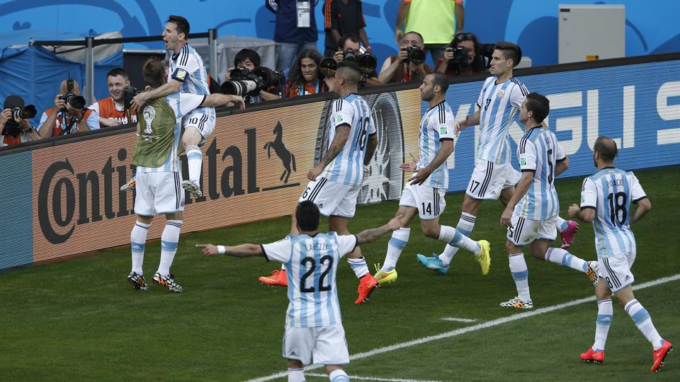 Lionel Messi is mobbed by his teammates after delivering a stoppage-time winner in Argentina's 1-0 win over Iran, one of his four group-stage goals.