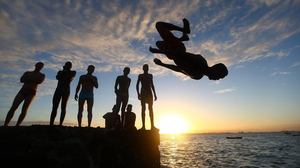 Boys dive off the dock in Porta da Barra in Salvador, Brazil.