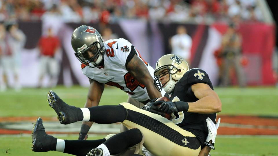 Safety Mark Barron and cornerback Rashaan Melvin of the Tampa Bay Buccaneers tackle New Orleans Saint tight end Jimmy Graham