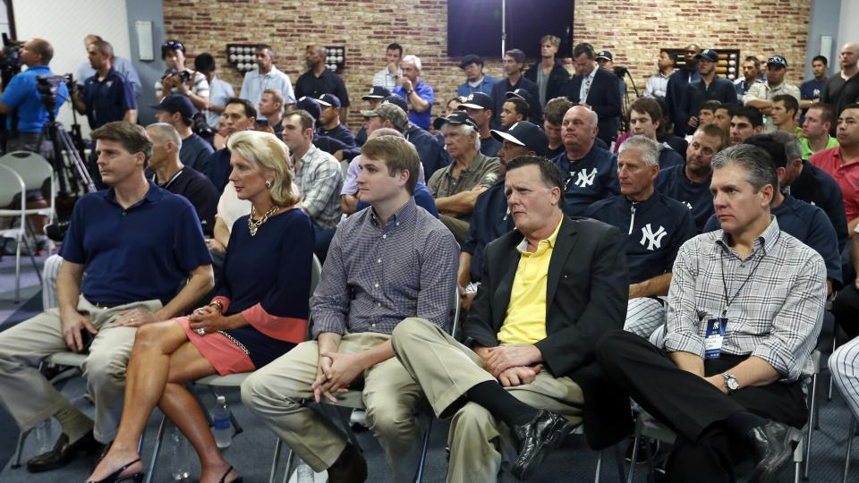 Agent Casey Close (L) listens to Derek Jeter speaking at media availability.