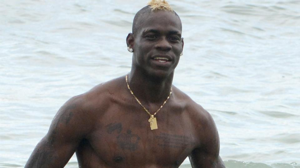 Mario Balotelli takes a selfie with two fans who abruptly ran onto the pitch