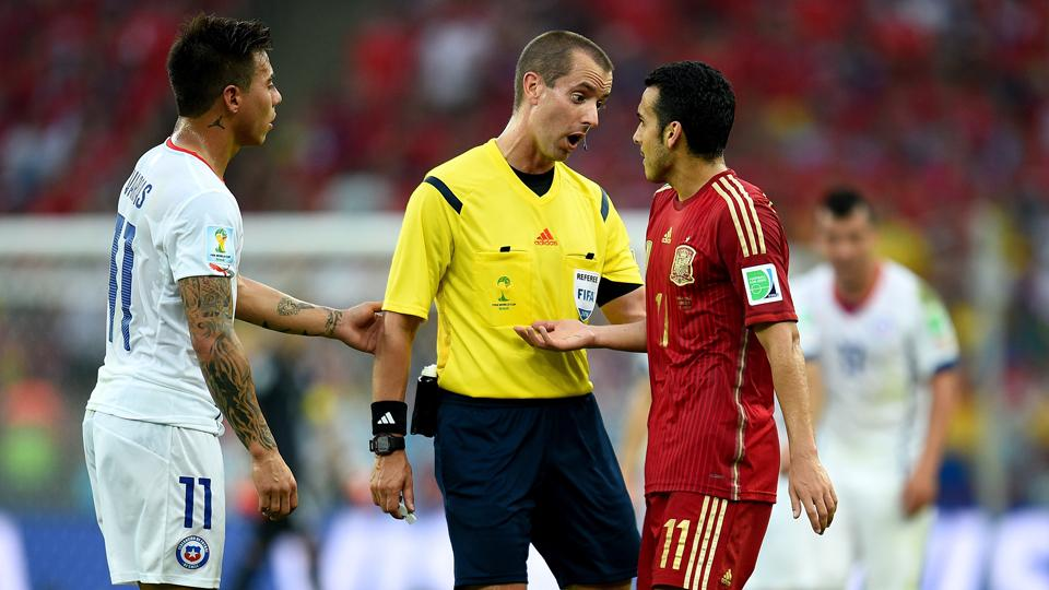 American referee Mark Geiger deals with Barcelona forward Pedro during Spain's World Cup group match against Chile.
