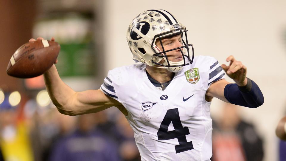 Taysom Hill of the BYU Cougars rolls out to pass against the Washington Huskiesin the Fight Hunger Bowl on December 27, 2013 in San Francisco, California. BYU will play a home-and-home with NIU starting in 2018.