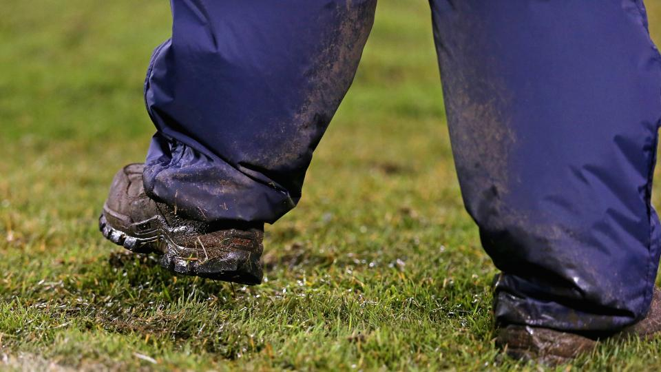 A worker tries to stomp down grass at Soldier Field during a game between the Chicago Bears and Baltimore Ravens on Nov. 17, 2013. The Bears are considering a switch to artifical turf.