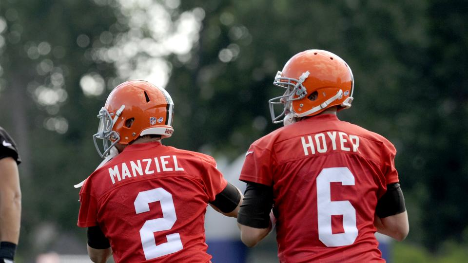 Quarterbacks Johnny Manziel and Brian Hoyer of the Cleveland Browns drop back to pass during a training camp practice at the Cleveland Browns training facility in Berea, Ohio on July 26, 2014.