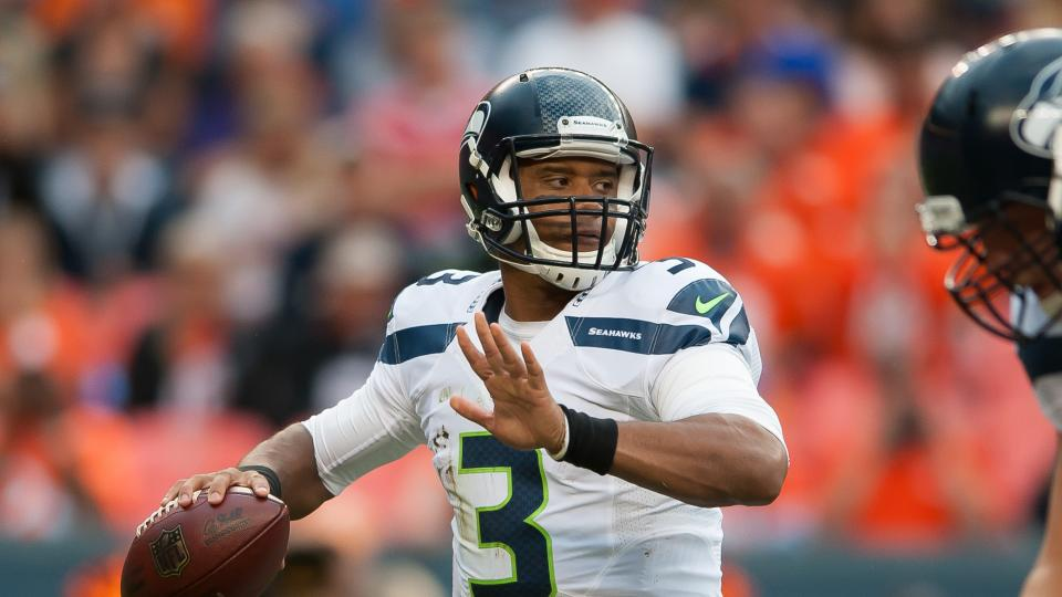 Quarterback Russell Wilson of the Seattle Seahawks sets to pass against the Denver Broncos during preseason action at Sports Authority Field at Mile High on August 7, 2014 in Denver, Colorado.
