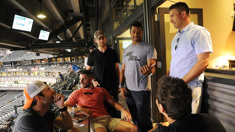 Russell Wilson's (center) inner circle includes his personal assistant and 'Chief of Staff' Matt Rodgers (left center) and childhood friend Scott Pickett (far left).